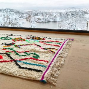 Azilal teppe i mål 160 x 92 cm. Vevd for hånd av kvinner i Marokko. Her får du et kvalitetsteppe som er lekent og klassisk på samme tid. Gir garantert hjemmet ditt litt farge og personlighet!
